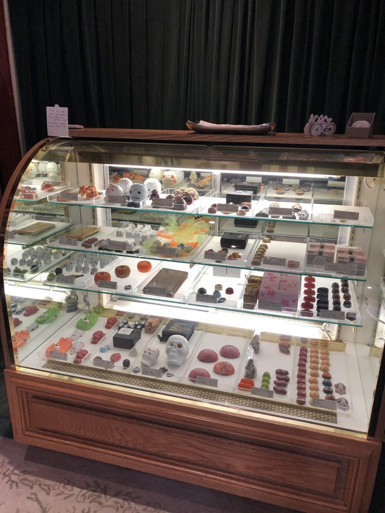 A display case with some of the amazing chocolate art by Sin Confections.